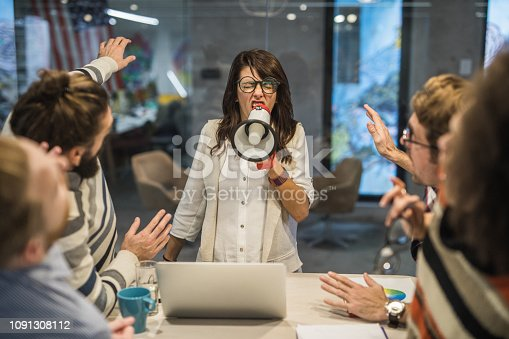 463813207 istock photo Rude female leader yelling at her coworkers through megaphone in the office. 1091308112
