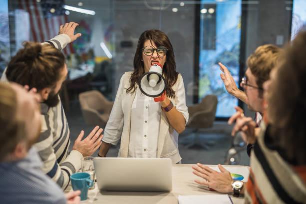 líder mujer grosera gritando a sus compañeros de trabajo a través del megáfono en la oficina. - mandón fotografías e imágenes de stock