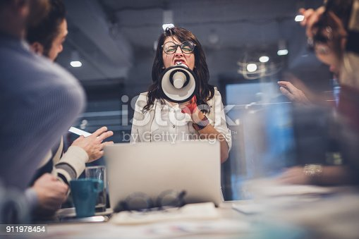 istock Rude female leader yelling at her coworkers through megaphone in the office. 911978454