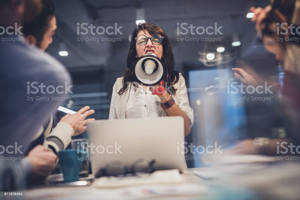 Rude female leader yelling at her coworkers through megaphone in the office. stock photo