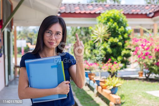 istock Rude funny Asian businesswoman rising middle finger outdoors 1140117520