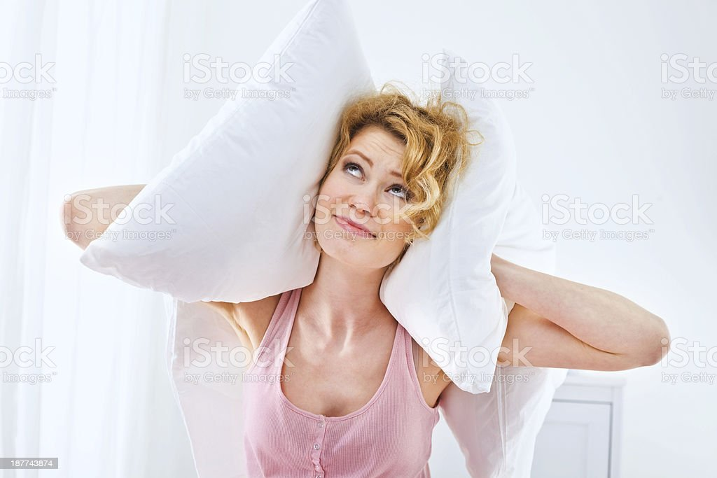 Rude neighbors Unhappy young adult woman squeezes pillows to her ears, can't sleep because of a big noise. 25-29 Years Stock Photo