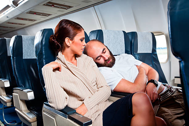 Rude passenger on the airplane Disgusted woman looking at the sleeping man sitting next to her, who rests his head on her shoulder. passenger stock pictures, royalty-free photos & images