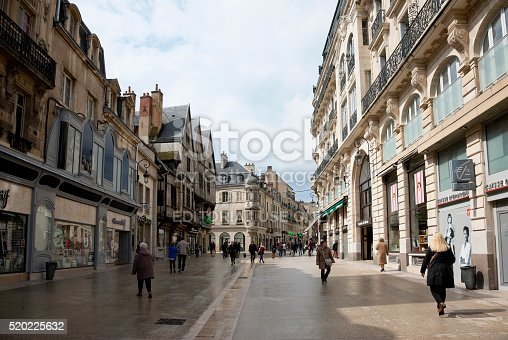 Dijon, France -- April 4, 2016: The Rue de la Liberté is the largest shopping street in the historic center of the French city Dijon. It connects the Place Darcy to the Place de la Libération. Pedestrians are walking along the street, shops, banks, cafes and restaurants are on the street. Early morning in bright April day.