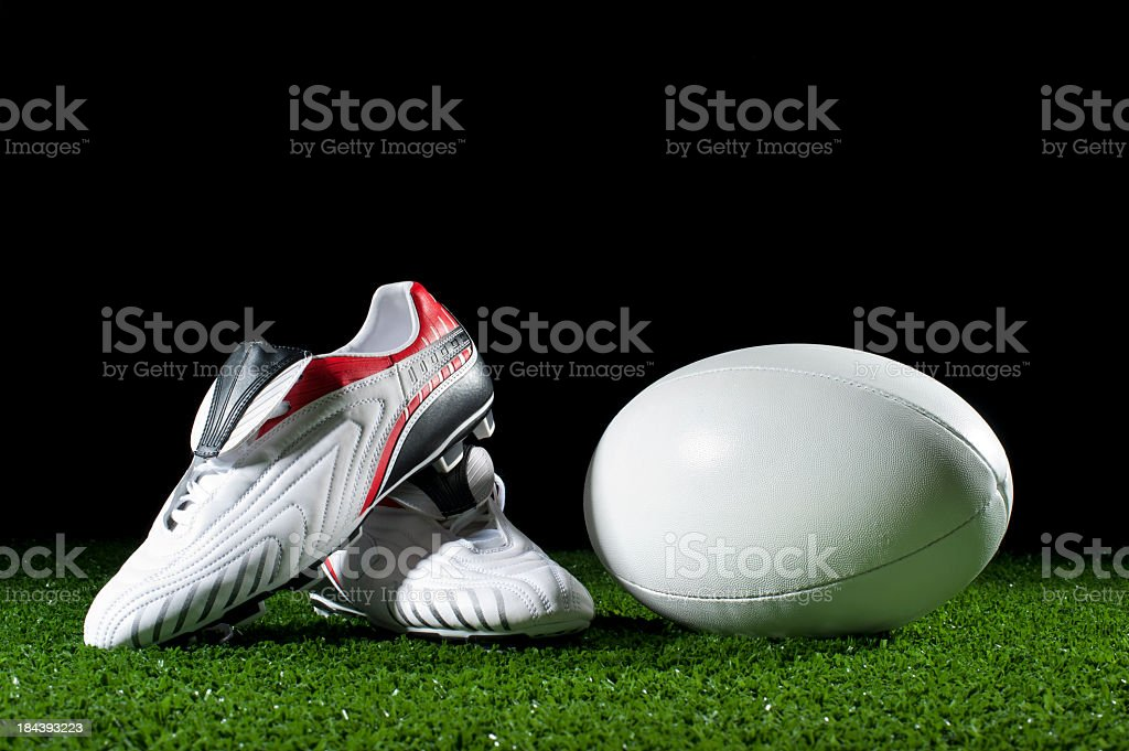 Rugby ball and boots on grass stock photo