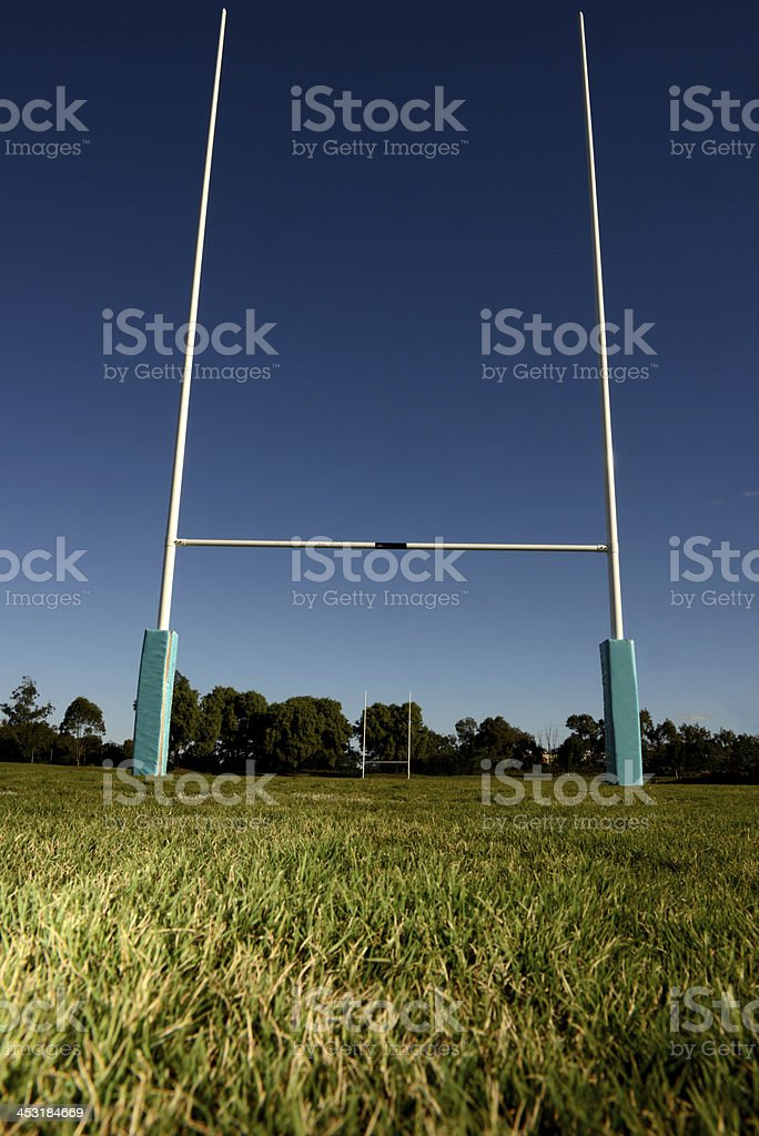 Rugby goal posts on a green field against a clear sky stock photo