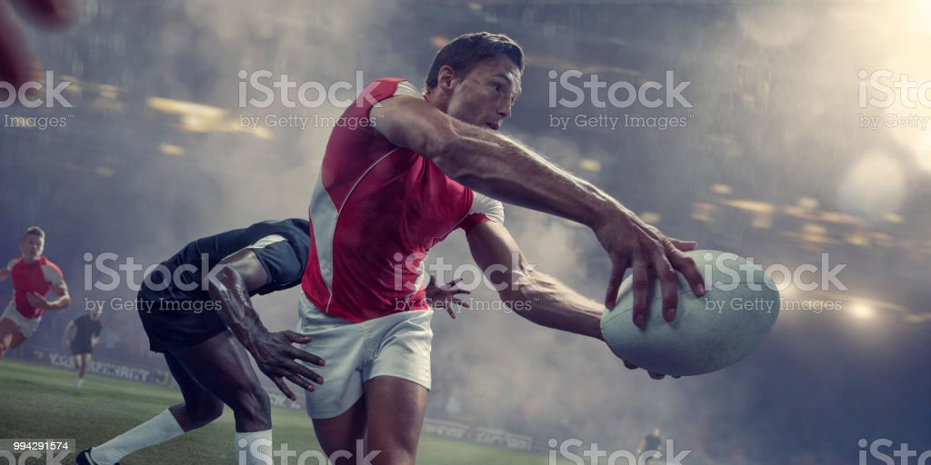 Rugby Player About To Pass Ball Just Before Being Tackled stock photo