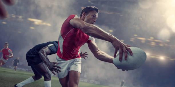 jugador de rugby a pasar la bola justo antes de ser abordado - rugby fotografías e imágenes de stock
