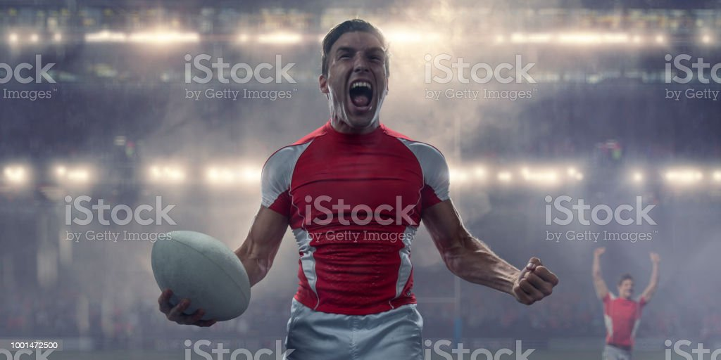 Rugby Player Holding Ball and Shouting in Victory Celebration stock photo
