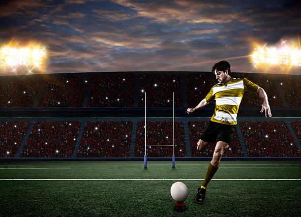 Rugby player kicking ball in illuminated stadium stock photo