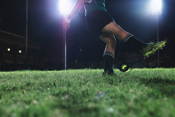 Rugby player kicking the penalty shot Rugby player kicking the ball from a tee for penalty shot. Legs of professional rugby player kicking the ball under lights at rugby stadium at night. studded stock pictures, royalty-free photos & images