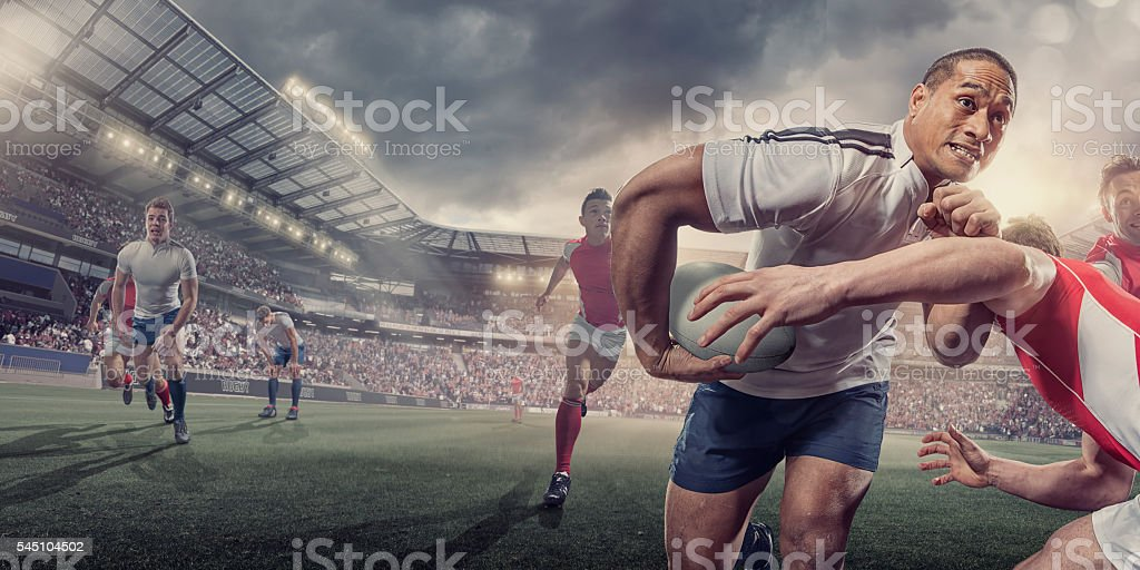 Rugby Player Running With Ball Whilst Being Tackled During Match stock photo