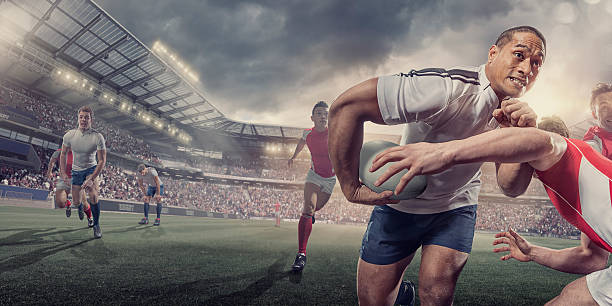 rugby-spieler läuft mit ball während angepackt während des spiels - rugby stock-fotos und bilder