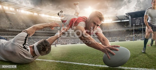 istock Rugby Player Scoring and Being Tackled in Mid Air Dive 505402328