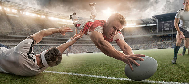 rugby player scoring and being tackled in mid air dive - rugby stock photos and pictures