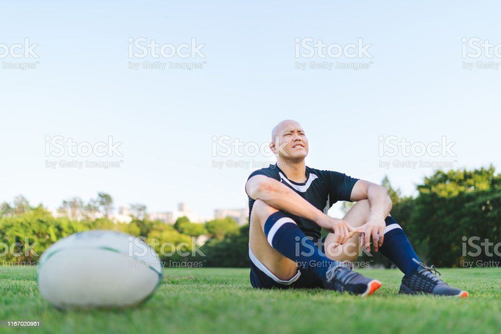 A rugby ball is put on grass field while a rugby player is sitting on...