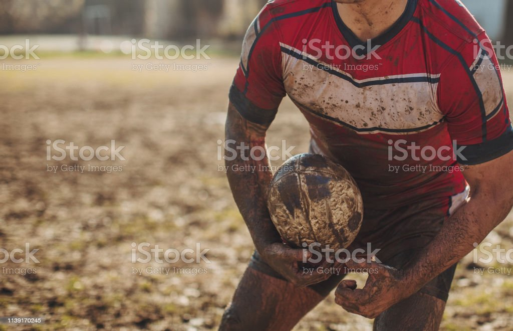 Rugby player standing on a plying field with ball in his hands.