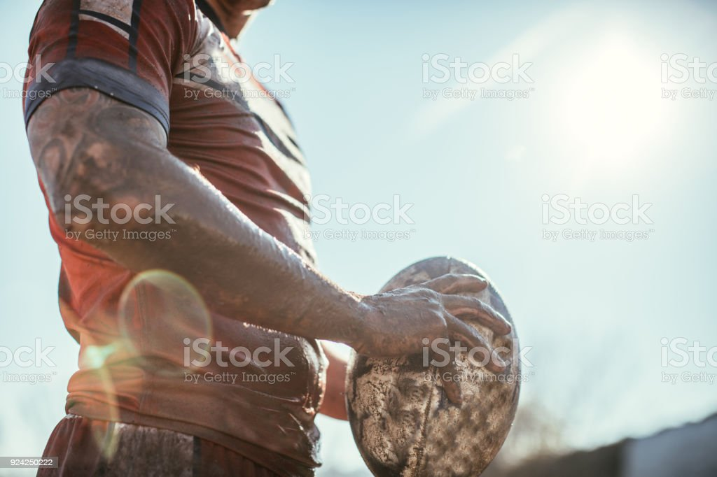 Rugby player standing on a playing field with ball stock photo