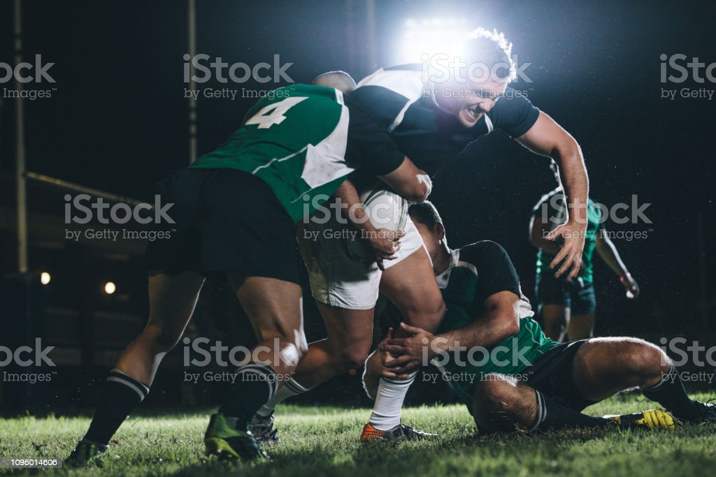 Strong rugby player trying to escape the tackle from opposite team....