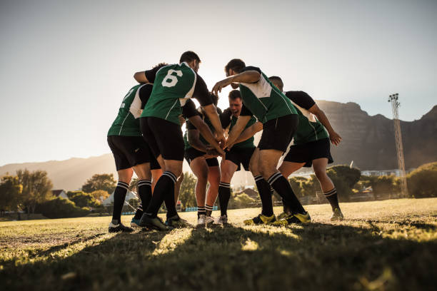 Rugby players cheering and celebrating win Rugby team putting their hands together after victory. Rugby players cheering and celebrating win. sport stock pictures, royalty-free photos & images