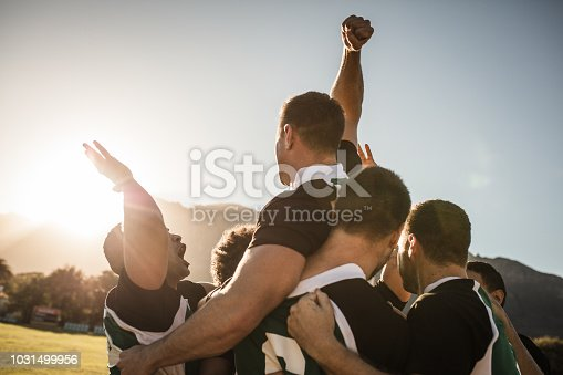 Rugby players lifting the teammate after winning the game. Rugby team celebrating the victory.