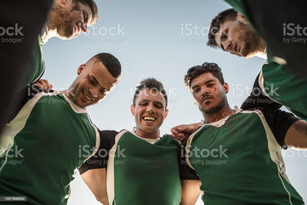 Low angle view of rugby players standing against clear sky. Rugby...