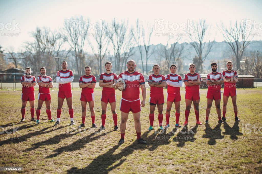 Rugby players standing on a plying field in a row. Sports jersey are...