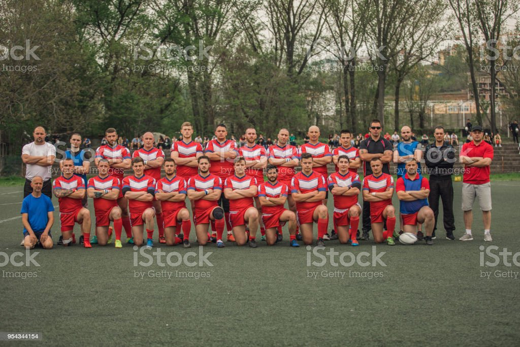 Group of people standing on the field, group photo of rugby team.