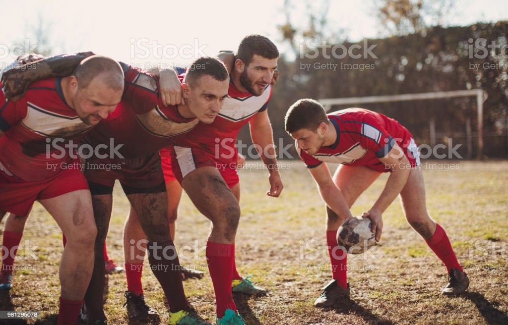 Young and strong rugby team on the field, group training outdoors.