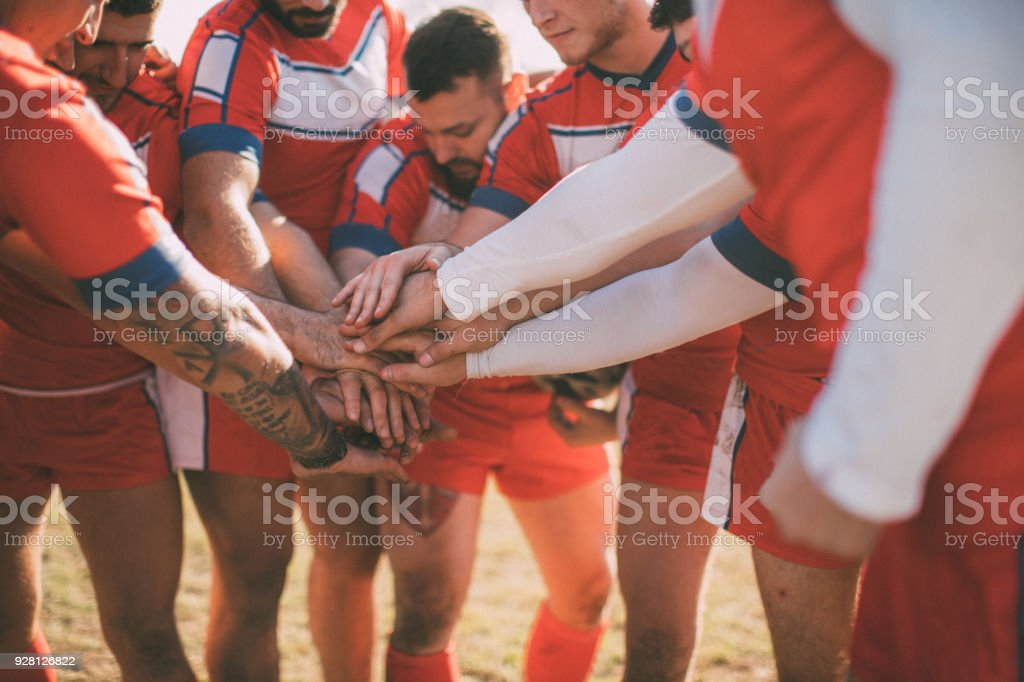 Young and strong rugby team on the field, holding hands all together.