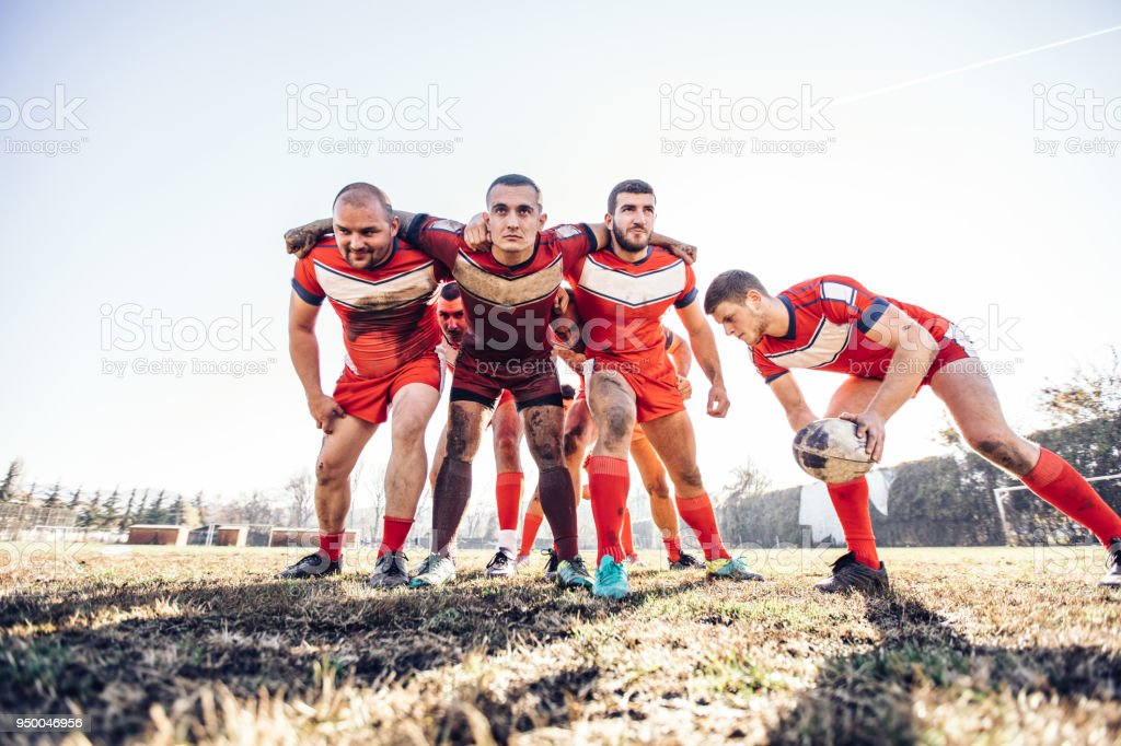 Young and strong rugby team on the field, rough group training.