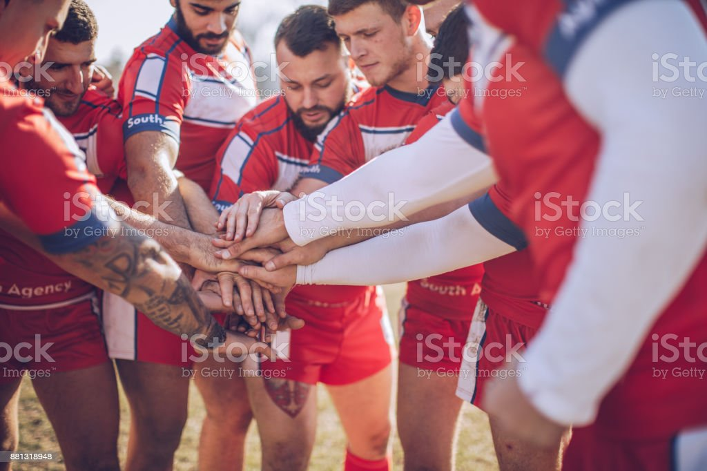 Young and strong rugby team on the field,holding hands all together.