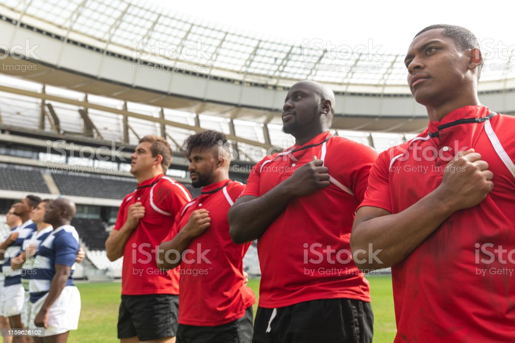 Front view of proud diverse rugby team taking pledge together in...
