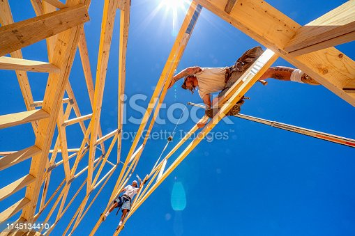 Rugged Carpenter on a Framing Crew Setting Trusses on a New Home