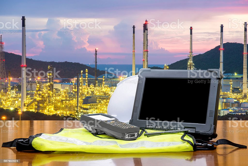 Rugged computers tablet in front of oil refinery stock photo
