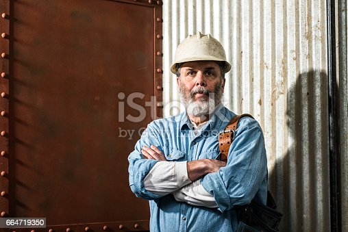 istock Rugged looking Middle-aged construction worker on job site 664719350