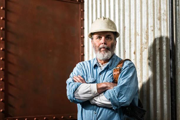 resistente mira mediana edad albañil en el lugar de trabajo - macho fotografías e imágenes de stock