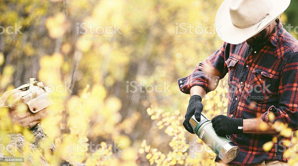 Rugged man breaks for coffee inHigh Western Grass stock photo