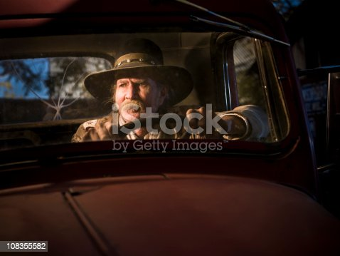 Western man sitting in cab of truck at sunset