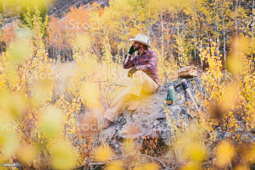 Rugged man sitting on rock in the woods of Montana stock photo