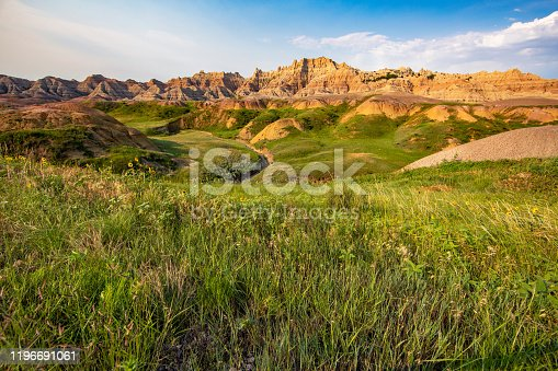 Rugged dirt and rock hills rise over a green grassed valley in the Badlands National Park in South Dakota.