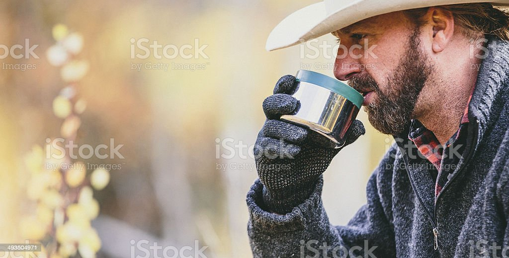 Rugged working man with beard drinks coffee while resting stock photo