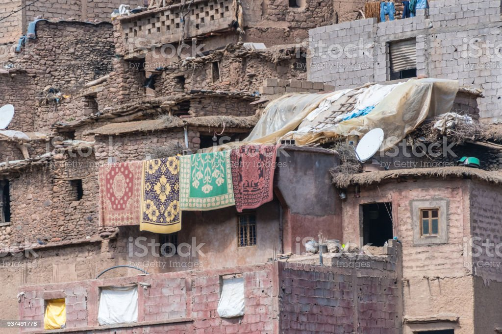 Rugs airing on a mountain side village in Morocco stock photo