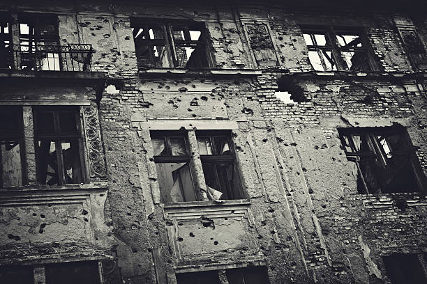 Ruin of War Residental building facade heavily damaged in the Balkans war. Toned image. bosnia and hercegovina stock pictures, royalty-free photos & images
