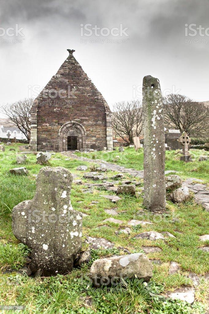 Ruined 12th Century Catholic Church in Ireland with ogham stone stock photo