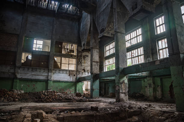 ruined abandoned interior of industrial hall - город призрак стоковые фото и изображения