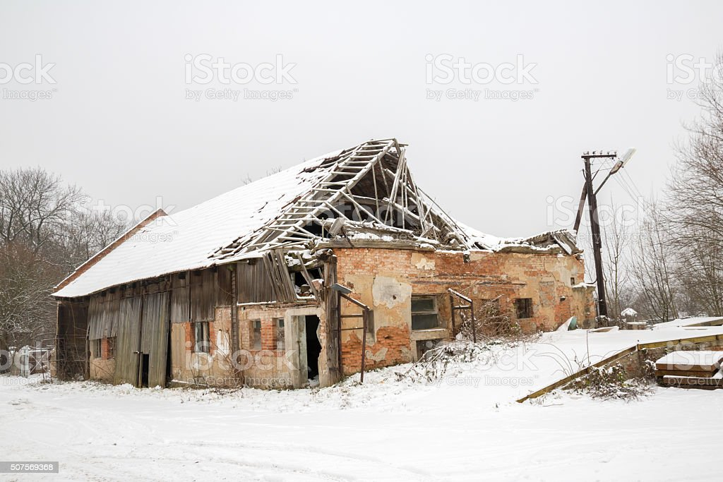 Ruined brick/wooden house, destroyed roof, in winter stock photo