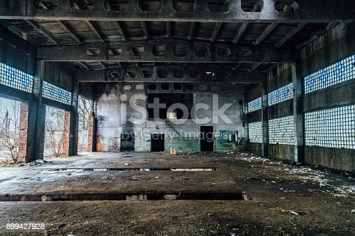 istock Ruined interiors of abandoned industrial hall. Charred walls 899427928