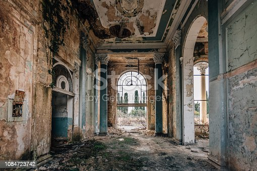 Ruined large hall interior overgrown by plants and moss.