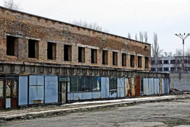 ruinen von einem backsteingebäude mit leeren fenster hinter einem zaun aus eisen - disaster design stock-fotos und bilder